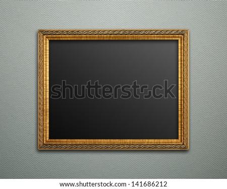 Empty golden vintage frame on wallpaper background - stock photo