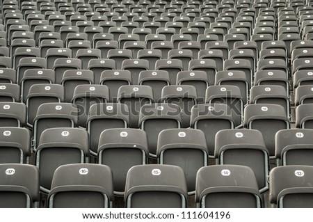 Empty gray plastic seats in a stadium. - stock photo