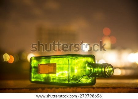 empty green Bottle of red wine lie on the table against night light urban scene background Transparent object on dusk street in city town backdrop Idea symbol of alcoholism ot trash   - stock photo
