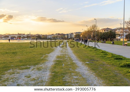 Empty green grass pathway for design during the sunset - stock photo