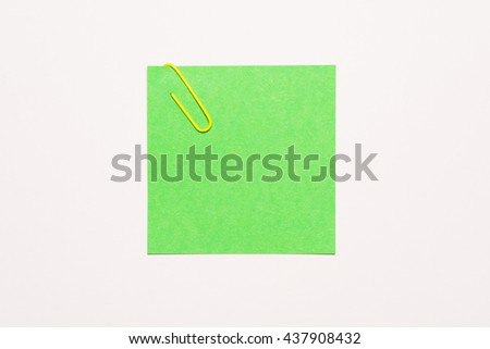 Empty green notepaper with yellow paper clip - stock photo
