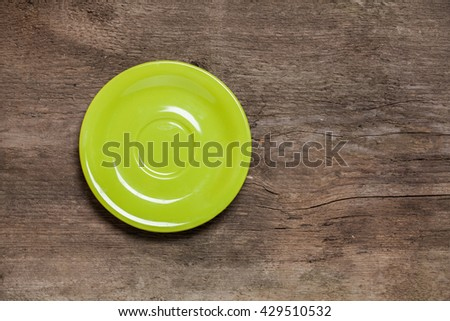 Empty green plate on wooden table. Top view. - stock photo