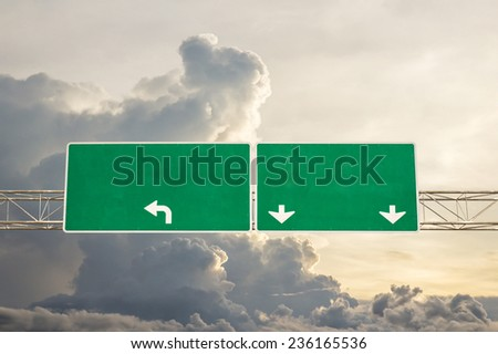 Empty green road sign against sky with clouds - a place for your own text on a green sign. - stock photo