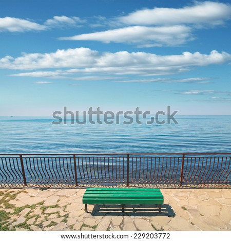 Empty green wooden bench stands on the sea coast in summer day - stock photo