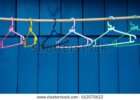 empty hangers against blue wall - stock photo