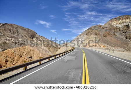Empty highway in deserted mountainous terrain, travel concept, USA.