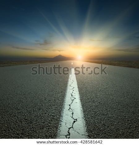 Empty highway leading to the mountains through the desert against the rising sun at beautiful sunrise. - stock photo