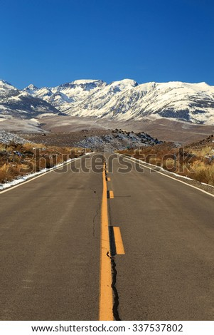 Empty highway with the Sierra Nevada mountains, California, USA. - stock photo