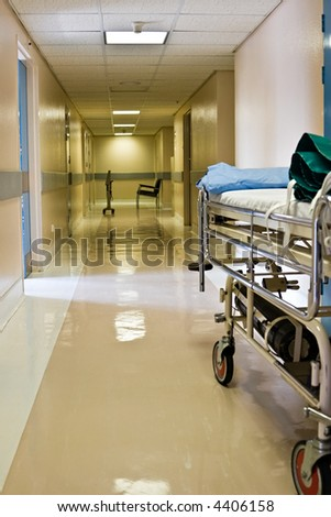 Empty hospital corridor, waiting chairs and bed