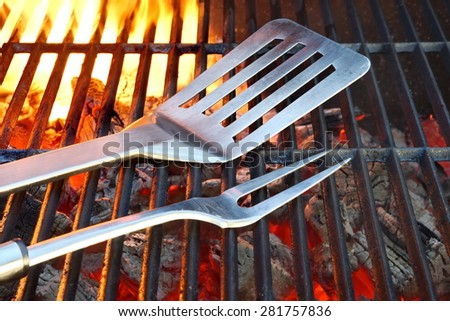 Empty Hot Flaming Charcoal Grill With BBQ Tools. Summer Outdoor Party Or Picnic Concept - stock photo