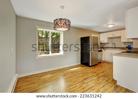 Empty house interior with furnished kitchen area. Kitchen with white cabinets and refrigerator. Kitchen with empty dining area