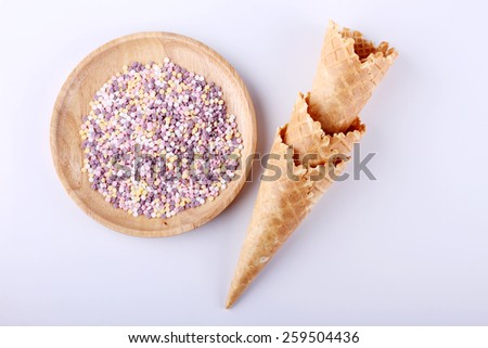 empty ice cream cones with colorful sprinkles on white background - stock photo