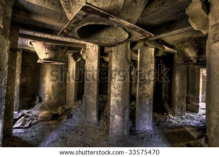 Empty industrial decayed room with large tube in the concrete wall - stock photo