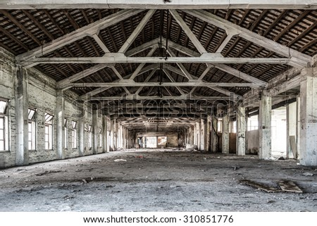 Empty industrial loft in an architectural background with bare cement walls, floors and pillars supporting a mezzanine