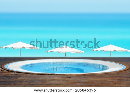 Empty jacuzzi facing a beach with a blue ocean - stock photo