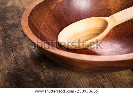 Empty ladle and bowl on dark wooden table - stock photo