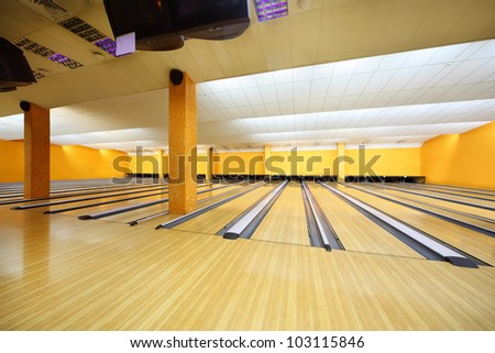 Empty light bowling club, lot of bowling lanes, yellow walls - stock photo