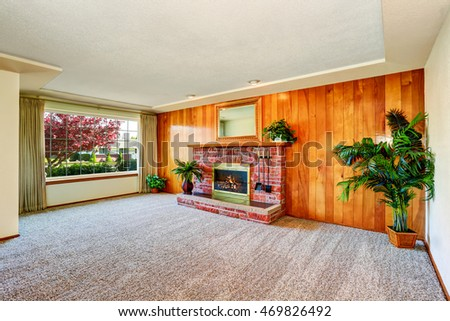 Empty living   interior with wood panel wall and fireplace with brick trim. Decorated with green tree in a pot. Northwest, USA