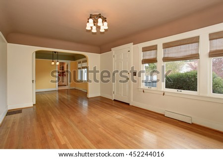 Empty living room interior with mocha ceiling, hardwood floor and white walls. View of arched doorway leading to other rooms.