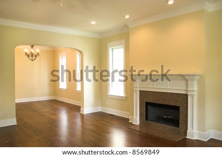 empty living room with granite fireplace and windows - stock photo