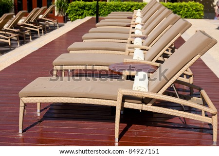 Empty lounge chairs in a row with towers - stock photo