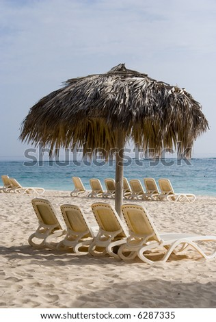 Empty loungers on a tropical beach with sunshade (Punta Cana, Dominican Republic) - stock photo