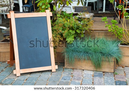 Empty menu advertising board and wooden box of grass near a restaurant - stock photo