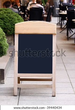 Empty menu board standing on the street and people seen eating on the blurred background - stock photo