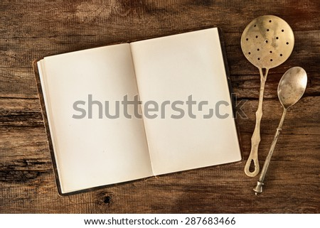 Empty menu or cookbook and vintage kitchen utensils on wooden table - stock photo