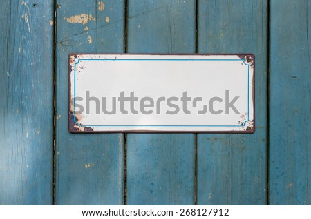 Empty metal sign in front of a wooden wall - stock photo