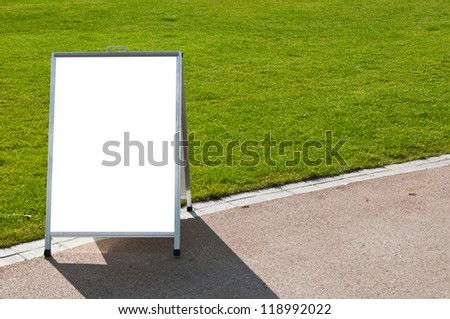 empty metallic board next to a grass field (isolated on white, focus on the grass) - stock photo