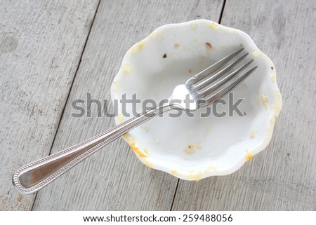 Empty mini casserole dish with fork on rustic wooden background - stock photo