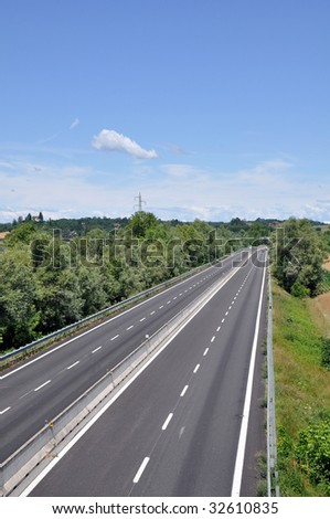 Empty motorway lanes with a blue sky - stock photo