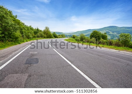 Empty mountain road in summer day. Blue sky over green hills
