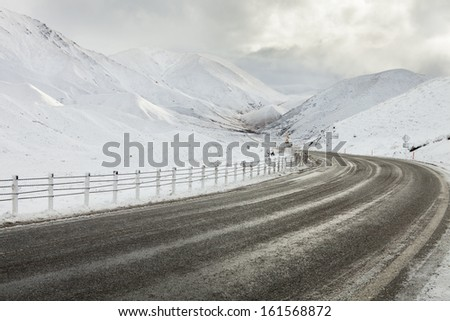 Empty mountain road on a cloudy winter day. South Island, New Zealand - stock photo