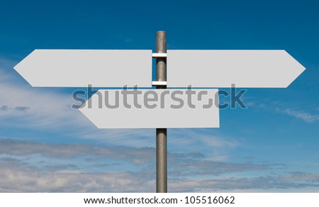 empty multidirectional sign against a blue sky background (boards isolated on grey) - stock photo