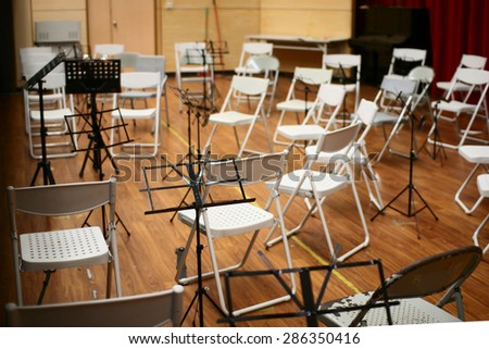 Empty music stand and chairs on stage. Selective focus on music stand. - stock photo