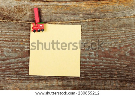 Empty note paper with clothes-peg in shape of train on old wooden background - stock photo