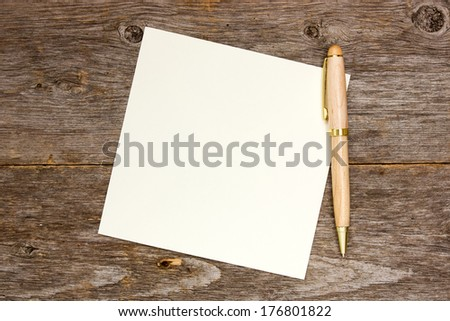 Empty note paper with pen on the wooden background - stock photo