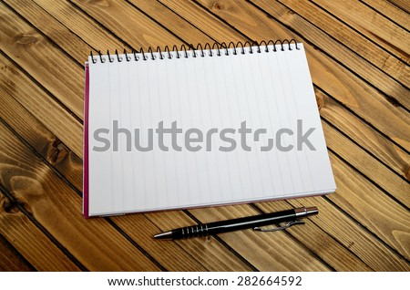 Empty notebook and pen on table - stock photo