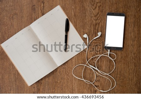 Empty notebook and phone  on wood background.