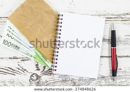 Empty notebook with money on wooden table - stock photo
