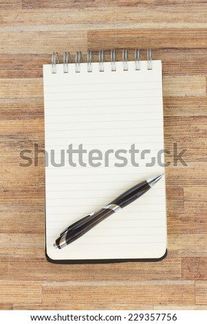 empty notebook with pen  on wooden table - stock photo