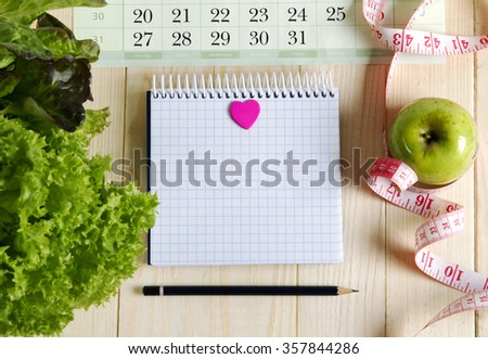 Empty notebook with vegetable salad and apple , heart, calendar on wooden table - stock photo
