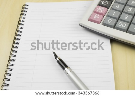 Empty notepad on office table with pen and calculator. View from above