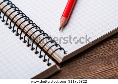 Empty notepad on wooden surface and red pencil