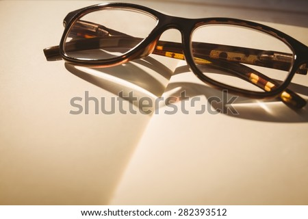 Empty notepad with reading glasses on a desk - stock photo