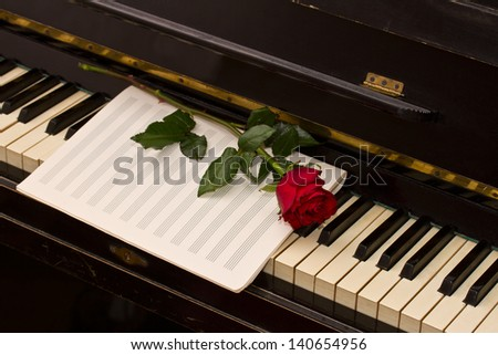 empty notes paper with one red rose on vintage piano - stock photo