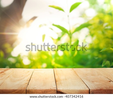 Empty of wood table top on blur of fresh green abstract from garden with sunlight .For montage product display or design key visual layout - stock photo
