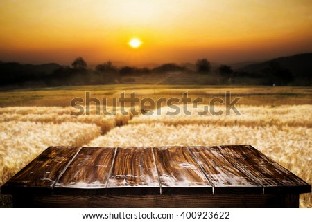 Empty of wooden desk space platform and barley agricultural field with sunset on background for product presentation. - stock photo